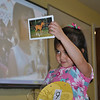 Shannon White holds up a picture in front of the video monitor of one of her favorite things — a horse — to share with her new friends in China.   (Crevier photo)