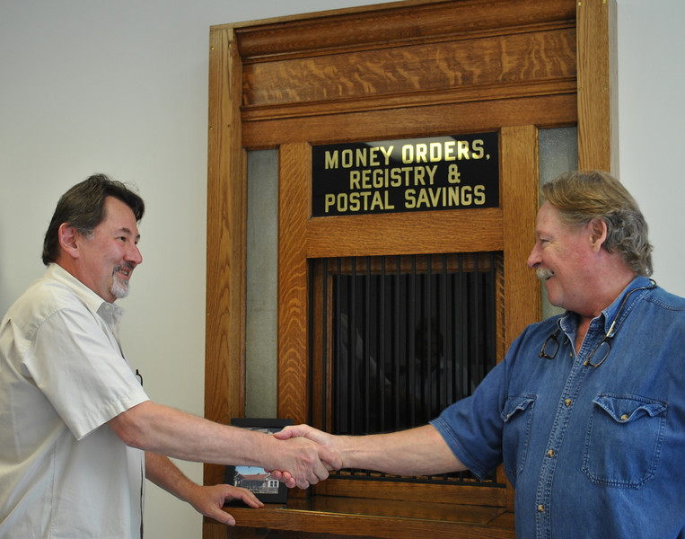 Hawleyville Post Office Postmaster Mark Favale, left, and woodwork expert Chris Jerace congratulate each other on a coordinated effort that has resulted in the 1929 stamp window behind them, salvaged from the former facility, being restored and erected inside the new post office on Barnabas Road.	(Crevier photo)
