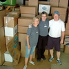 Pam McLaughlin, left, and her husband Pat, right, stand with fellow volunteer Maria Roy in front of the remaining boxes filled with donated shoes for Soles4Souls, which were headed to Tennessee to outfit needy individuals in the US and abroad in the coming weeks. The trio had already completely filled one box truck with about half of the 10,019 pairs of shoes that were collected during a townwide effort this spring and were getting ready to load truck number two on May 12.  (Voket photo)