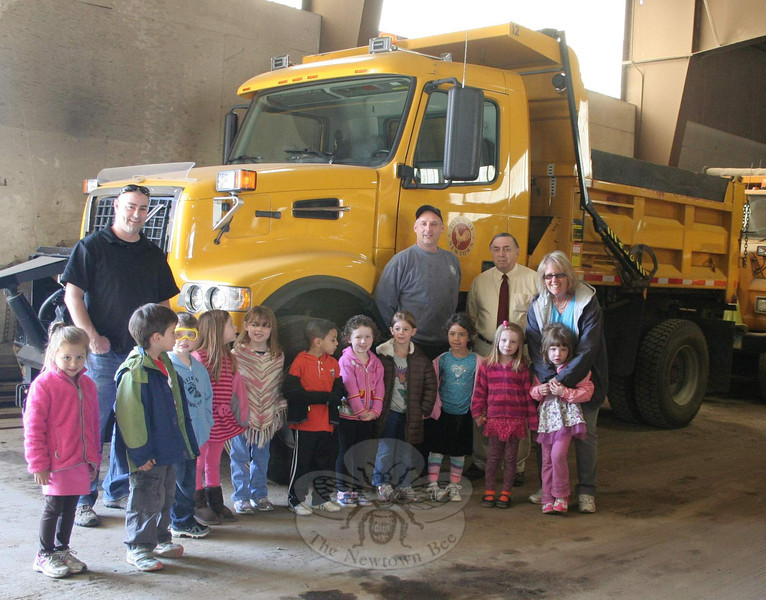 Students and faculty from Newtown Congregational Preschool School recently visited the Public Works Highway Department headquarters recently, and enjoyed a tour led by Public Works Director Frederick Hurley. Mr Hurley, second from right, showed the group aerial maps of Newtown, and the children were able to find their school on the map. Mechanic Tim Whalen, third from right, showed everyone where the town trucks and police cruisers are serviced, and allowed the children to climb into the cabs of one of the trucks. The Wednesday morning outing was one of the many community field trips the school offers.   (Hicks photo)
