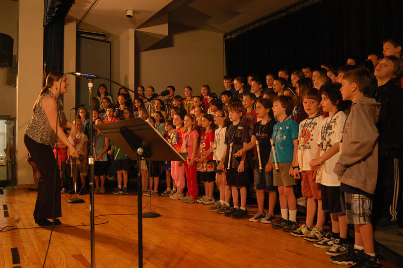 Hawley Elementary School's music instructor Cynthia Holberg, left, led the fourth grade chorus members through a school assembly on Monday, May 14, when the students rehearsed for their then upcoming Spring Chorus Concert, scheduled for May 21. Students took turns introducing different pieces, from Irving Berlin's Blue Skies to Ludwig van Beethoven's Ode to Joy.  (Hallabeck photo)