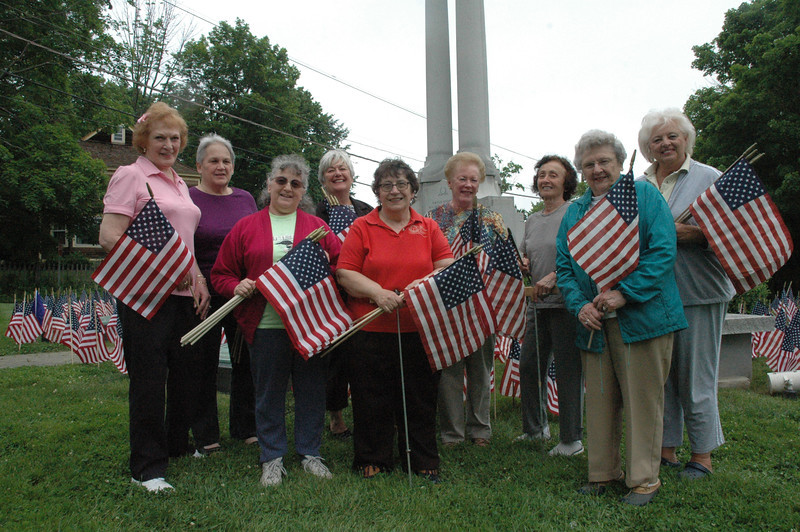 On Friday, May 25, members of the Newtown Woman's Club (GFWC/CT) placed US  flags at the Soldiers and Sailors Monument on Main Street as a Memorial Day tribute to the local people who have served and are serving as members of the US Armed Forces. It is the fourth year that the club has conducted the decoration project. This year, the club added flags for each branch of the armed forces and for the POW/MIA military. Commander Jamie Rebman of Newtown VFW Post 308 donated the flags. Shown, from left, are club members Carol Mattegat, Pat Denlinger, Betty Warner, Marilyn Alexander, Marion Thompson, Marie Sturdevant, Millie Anderson, Jean Smith, and JoAnn Bruno.                 —Bee Photo, Gorosko