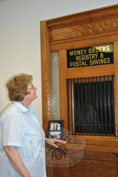 Retired officer in charge of the Hawleyville Post Office Jane Payne admires the newly restored stamp window, Wednesday, May 30, through which she passed thousands of stamps to customers when it was operational.   (Crevier photo)