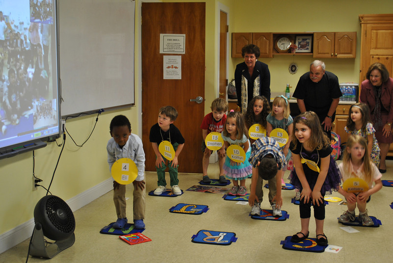 In the background, from left, St Rose Principal Mary Maloney, Monsignor Robert Weiss, and Bridgeport Diocese Schools Superintendent Margaret Dames join with St Rose preschoolers, during a Skype event, in performing a silly action song for children in China.   (Crevier photo)