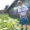 Daniel Jaeger watered one of the raised garden beds at Sandy Hook School on Wednesday, July 11, during a Garden Party hosted by Sandy Hook School teachers Dawn Ford and Kris Feda.  (Hallabeck photo)