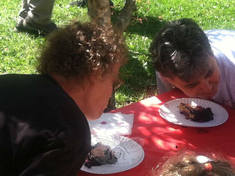 """Linda Whippie, left, and Sheila Cole, hands behind their backs, dive into their slices of blueberry pie at the pie eating contest held at the September 9 Newtown Congregational Church """"Welcome Back"""" picnic. Ms Whippie received second place. Third place went to winner Trent Harrison's daughter, Morgan.  (Crevier photo)"""