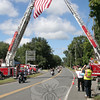Organizers of The 12th Annual CT United Ride believe more than 2,400 flag-wielding motorcyclists gathered on Sunday, September 9, to participate in this year's event. The fundraiser starts in Norwalk and travels through ten towns before ending at Seaside Park in Bridgeport. The 60-mile route brings riders, and in many cases passengers, into Newtown via Route 302 from Bethel. Riders follow Route 302 to its intersection with Route 25, and then travels south, heading into Monroe. While in town the participants ride past the firehouses in Dodgingtown and Botsford, where firefighters had gathered to salute the riders. On Main Street South just south of Borough Lane, members of Hook & Ladder and Sandy Hook's fire companies used their ladder trucks to raise a 20- by 30-foot American flag over the roadway. Funds raised through fees paid by riders and their passengers are donated to Connecticut firefighters and police officers, and two chapters of the United Way.   (Hicks photo)