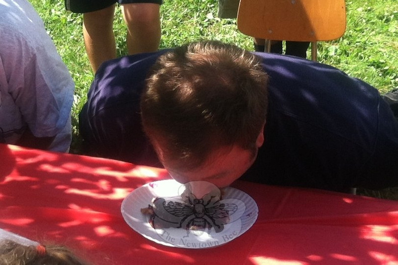 """Trent Harrison licks his platter clean to win the blueberry pie eating contest at the Newtown Congregational Church """"Welcome Back"""" picnic, Sunday, September 9. Following his win, Mr Harrison planted a blueberry kiss on the cheek of pie contest organizer Liz Eaton.    (Crevier photo)"""