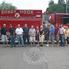 "The Second Annual SHOP Passport To Sandy Hook will be offered in Sandy Hook Center in just a few weeks. Among those organizing and/or participating in the event this year are, from left, Chuck Kilson, Andy DeWolfe, Joe Hemingway, Randy Muller, Ed Raymond, Karin Halstead, Sharon Doherty, Bill Halstead, Mike Burton, Ryan Clark, Rob Manna, Maribeth Hemingway, and Tamara Doherty. Sandy Hook Volunteer Fire & Rescue will have two fire trucks at the event, one for a ""Touch-A-Truck"" opportunity and the other to serve as a drop-off point for FAITH Food Pantry donations.   (Hicks photo)"