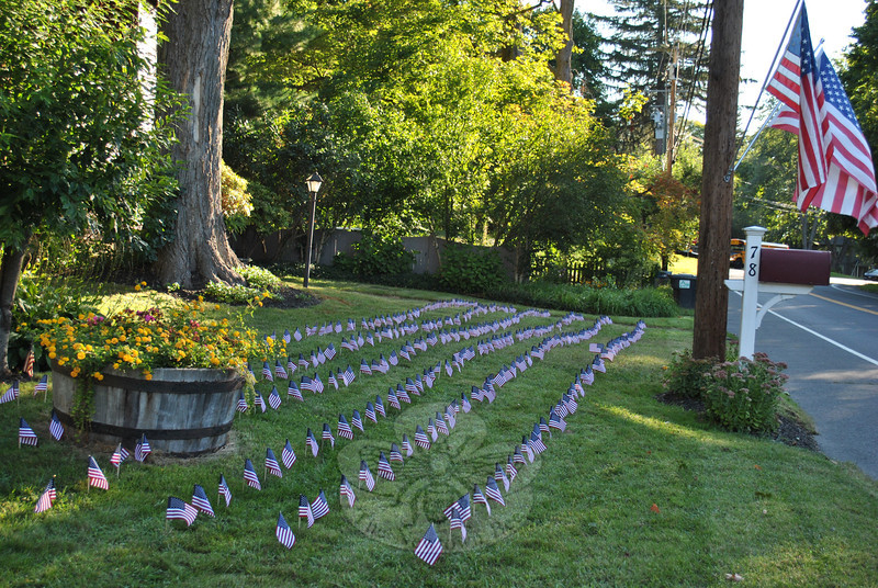 Commuters passing by the Bryant home at 78 Main Street on Tuesday morning, September 11, were greeted by a field of 360 American flags lining the lawn, and two full-sized flags waving from posts above the mailbox.  (Crevier photo)