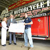 Newtown Savings Bank Customer Service Representative Barbara Tucker, left, stands with bank Manager Ryan Storms and Hook & Ladder Company No. 1 member Tim Hoeffel as they present Mr Hoeffel with a $1,000 donation to the fire company's effort to raise funds for a new firehouse.   (Bobowick photo)