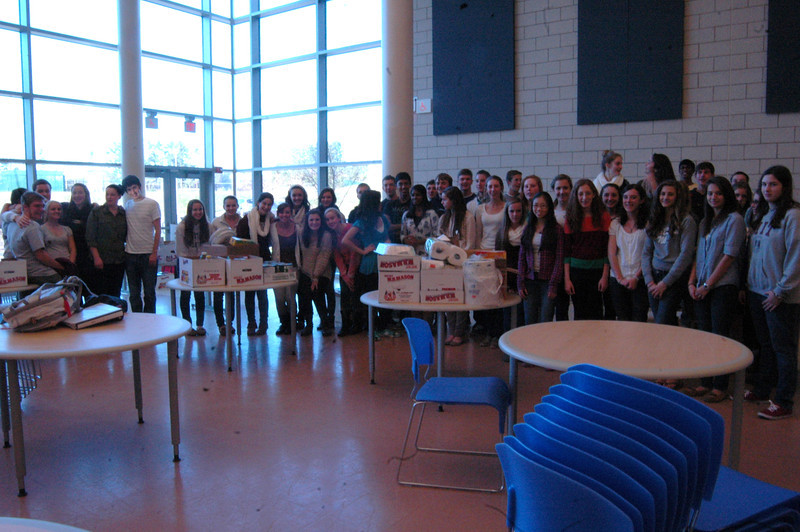 Members of Newtown High School's Executive Class Council, Spanish Club, and Interact Club worked on Monday, November 19, to separate and sort the food donated through the school's food drive to be given to both the Women's Center of Greater Danbury and to Newtown's Social Services Food Pantry.   (Hallabeck photo)