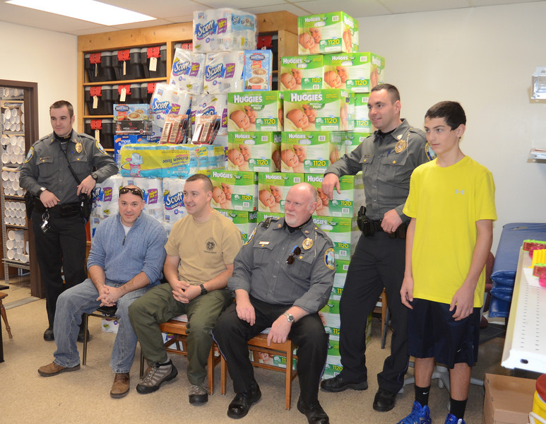 A number of volunteers pitched in on November 24 to assist Officer Matthew Hayes, seated center in T-shirt, and the Newtown Police Union packing care packages for the Connecticut National Guard's 143rd Military Police Company of West Hartford. Officer Hayes was a member of that unit for nine years, including a period of deployment to Iraq in 2003. Joining him, from left, are Officer Liam Seabrook, Officer Scott Ruszczyk who is also the local union president, Officer Robert Haas, Officer Ben Mulhall, and Ryan Norton.    (Voket photo)