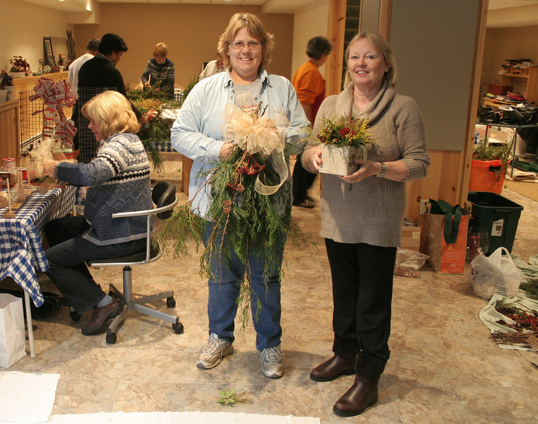 Garden Club of Newtown Co-President Holly Kocet (left), shows one of the swags that will be offered during this weekend's annual greens sale, while Co-President Kathy Williams holds a birch bark planter. Club members spent hours at the home of Kim Verdries on November 27, putting together and arranging many of the items the club will sell during its largest annual fundraiser this coming weekend.   (Hicks photo)