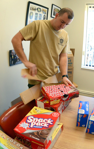 Newtown Officer Matthew Hayes opens a case of pudding cups to separate into several care packages being sent to his former colleagues in the Connecticut National Guard's 143rd Military Police Company who are currently stationed in the Mideast. Residents can continue to donate nonperishable food items and toiletries through a collection box in the police headquarters lobby. Toilet paper and wet wipes are desperately needed.   (Voket photo)
