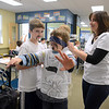 Teacher Carla Tischio aims Garrett Wolf toward a picture where he tries to accurately place a paper mustache. Her cluster, along with all Reed students, took part in a recent Mustache Day fundraiser to make a contribution to the Red Cross in its efforts to aid Hurricane Sandy victims.  (Bobowick photo)