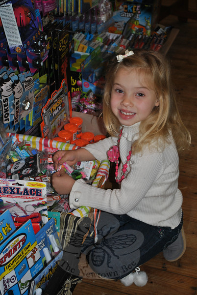 Alexa Schmid, 4½, looks over a display of small toys at her mother's Sandy Hook shop. Tracy Schmid, owner, says that it is important for local money to be spent locally, and for businesses to support each other.  (Crevier photo)