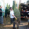 Firefighter Nick Cerreta transfers a tree from the truck to the lot last week. Trees and other decorative holiday greens are now for sale at the Sandy Hook Volunteer Fire & Rescue Company on Riverside Road. (Bobowick photos)