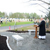 Monsignor Robert Weiss offers thankful words about the military veterans and a new me-morial in place before him, thanks to Matthew Rahtelli, who completed the work at the St Rose Cemetery as his Eagle Scout project.   (Bobowick photo)