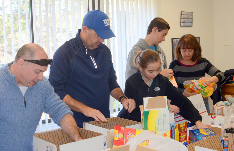 Officer and local Police Union President Scott Ruszczyk, left, was joined by Monroe Police Officer Todd Keeping and his family to assemble care packages last weekend for Connecticut National Guard troops.   (Voket photo)