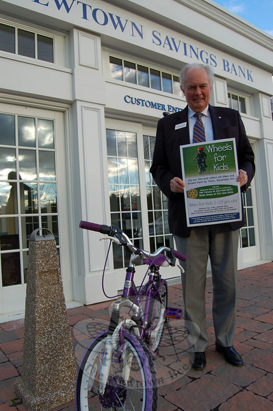 The Newtown Rotary Club is collecting used wheeled toys, trikes, sidewalk bikes, big wheels, bicycles, and BMX bikes to donate to Wheels for Kids, an activity of Danbury Youth Services that provides bikes to local people in need. Shown here is Newtown Savings Bank Assistant Vice President Brian Amey with one of the already donated bikes to announce the program. Mr Amey and Pat Caruso are both willing to collect used bikes from residents if they call Mr Caruso at 203-426-8870 or Mr Amey at 203-364-2906 to arrange a pickup.  (Hallabeck photo)