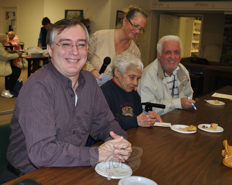 From left are Judges Gus Thanasoulis of Senior Helpers, Nunnawauk resident Minerva Binaco, and John Taggart of Starion Energy as they get started on rating the 13 entries in the Nunnawauk Meadows Apple Bake Off on November 17. Residents' Association President Linda Schettino looks over Ms Binaco's shoulder as she marks her choice.  (Crevier photo)