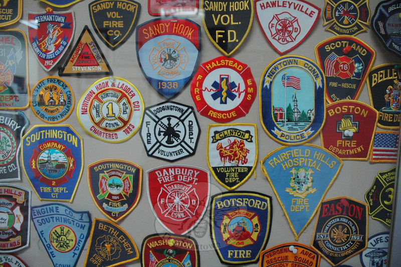 Besides the many shoulder patches that Sandy Hook volunteer firefighters have received from other emergency units since 12/14, these patches are some of the many other patches that are planned for display in the new cases.   (Gorosko photo)