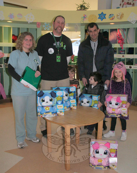 A call from Chris Wenis, second from the left, to Geoff Roesch to thank the toy inventor for creating a toy that helped Mr Wenis's child begin sleeping again after 12/14 resulted in a cross-county trip and the donation of dozens of Starshine Watchdogs for Newtown students. Wende Wenis, on the left, began searching for something that would help her son, and the couple were surprised to find a toy that could do the trick. Mr Roesch recently donated a few hundred of the toys to children in Newtown, including those who attend The Children's Adventure Center. Continuing to the right in this photo is Jakob Wenis, peeking out from behind his father; Drilon Lena and his father, Ylli; and Allison Nowacki. To read more about the arrival of Starshine Watchdog in Newtown, visit NewtownBee.com.    (Hicks photo)