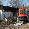 A worker used a small excavator on April 8 to demolish a vacant house at 12 Queen Street. New construction is planned for the site where orthodontist Curtis H. Beck, DMD, plans to build a new office. The doctor currently is working in a temporary structure at the property.   (Gorosko photo)
