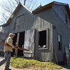 Greg Rosengren approaches the barn that he is restoring at 38 Main Street. The building had been sagging to one side and suffers from rot and structural deterioration.   (Bobowick photo)