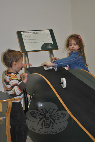 "Noah Beninati of Easton and Sophia Byl of Southbury have fun racing wheels down a sloped track, Saturday, April 6, during opening day of the EverWonder Children's Museum ""EverWonder Experience.""   (Crevier photo)"