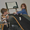 """Noah Beninati of Easton and Sophia Byl of Southbury have fun racing wheels down a sloped track, Saturday, April 6, during opening day of the EverWonder Children's Museum """"EverWonder Experience.""""   (Crevier photo)"""
