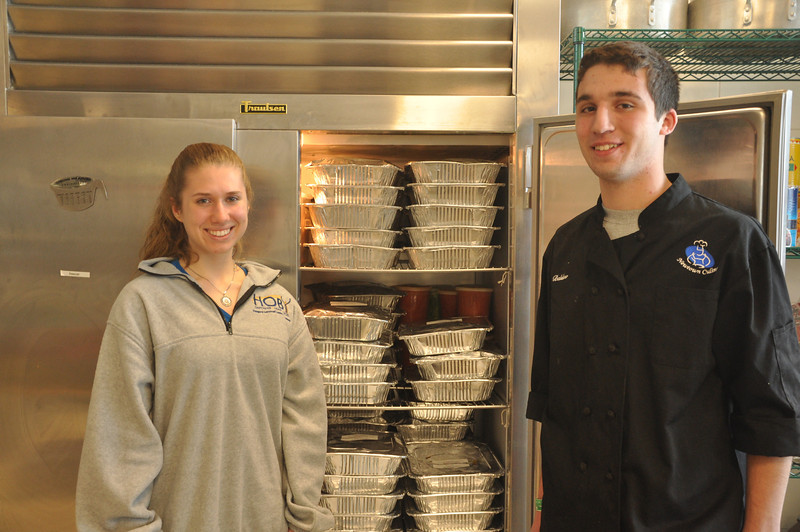Sonya Stranczyk and Matt Baldino stand in front of trays of prepared food in the Newtown High School's culinary department. Since September a group of NHS students, with the help of faculty and administration, has been putting time and energy into creating a program that has provided thousands of meals for area homeless shelters. The pilot program called Feeding The Need is the brainchild of Miss Stanczyk, who is the director of the program.    (Dietter photo)