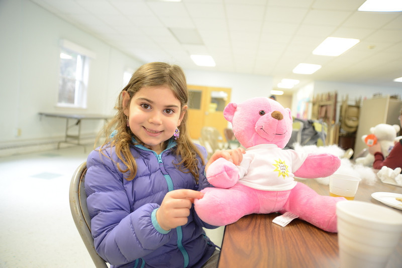 Daniella Crisci props up Rose, a stuffed bear she made recently at a free workshop for children.   (Bobowick photo)