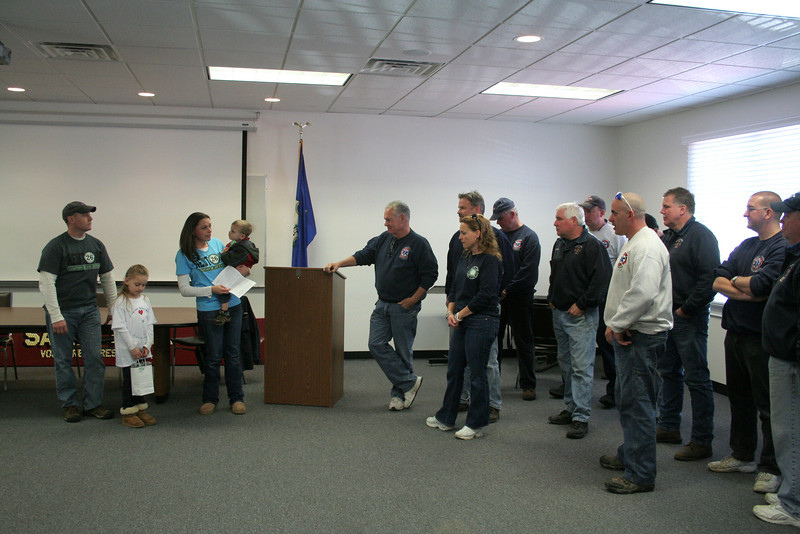 Speaking as a Sandy Hook resident, the mother of two children, and wife of a Bridgeport firefighter, Kristen Boroskey, third from left, thanked Sandy Hook firefighters for being part of the effort of recovery following 12/114. Bridgeport firefighters have launched The 26 Sandy Hook Angels Fund, and are hoping to help pay for a carousel to be gifted to the Town of Newtown. With Mrs Boroskey is her husband Paul and the couple's children, Madison and Will.   (Hicks photo)