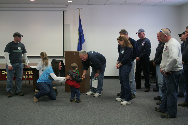 Once his mother finished her remarks, Will Boroskey very tentatively approached the chief of Sandy Hook Volunteer Fire & Rescue, presenting Mr Halstead with a box of 26 Sandy Hook Angels auto decals.   (Hicks photo)