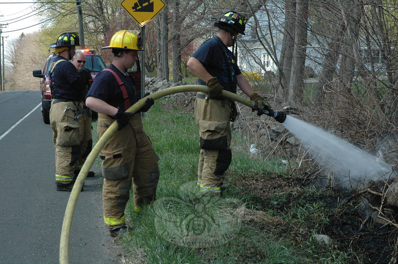 Sandy Hook and Botsford volunteer firefighters responded to two brush fires in Sandy Hook about 2,000 feet apart early on the afternoon of April 26. It is thought that a surge of current in suspended electrical lines caused equipment failures which resulted in the fires occurring in brush on the ground below the lines. The fire pictured occurred on the north side of Berkshire Road near its intersection with Great Ring Road. From left is Firefighter Richard Conrod, Chief Bill Halstead, and Firefighters Andy Ryan and Karl Sieling, Jr. The other fire took place on the west side of Great Ring Road near its intersection with Erin Lane.   (Gorosko photo)