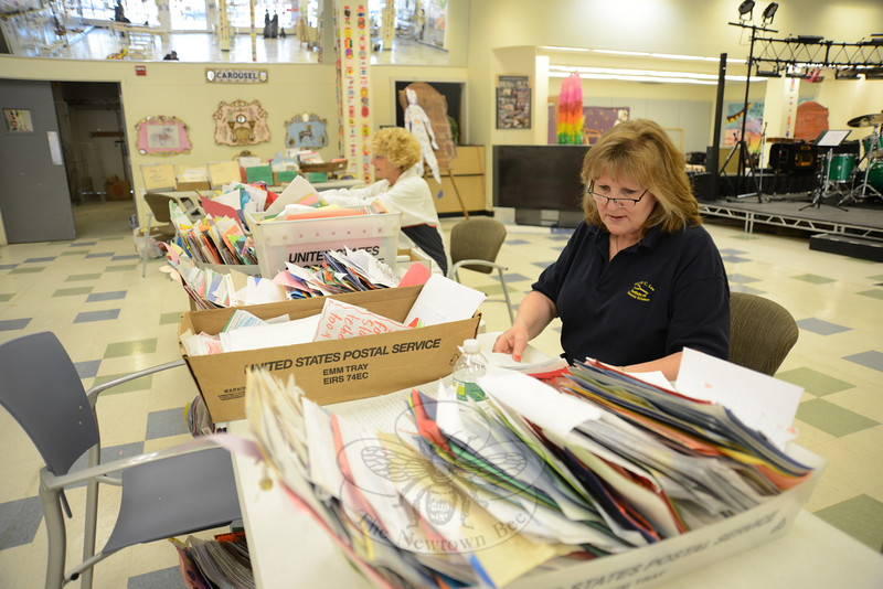 Volunteers Wendy Hartley-Morris, right, and Eileen Berry both sort mail still flowing into town in the wake of 12/14.  (Bobowick photo)