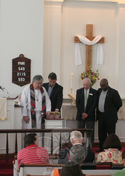 The Reverend Mel Kawakami, senior pastor of Newtown United Methodist Church, blessed two dozen copies of Strength for Service to God and Country before they were presented to members of the Sandy Hook church on April 28. With him, continuing left, is the Reverend Ken Kieffer, Jon Christensen, and Royston Bailey.   (Hicks photo)