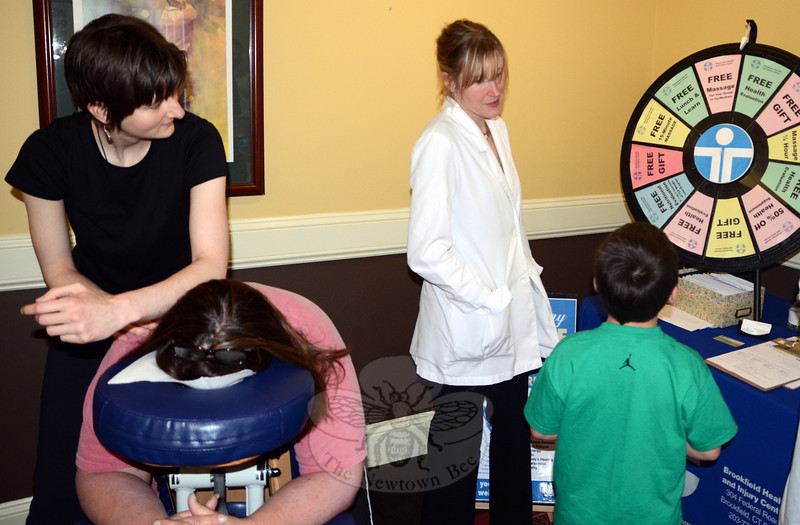 Mary Ellen Barnett, left, of Physicians Health & Injury Center gave Destination Newtown vendors and attendees a chance to spin a prize wheel for free giveaways while Jessica Myers-Bittner dispensed chair massages.  (Voket photo)