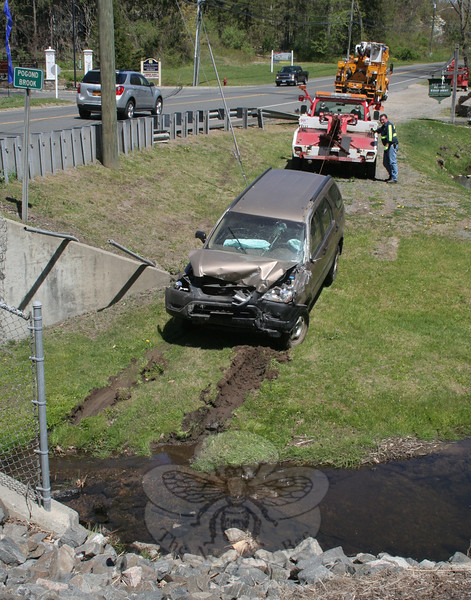 Police said they received a report about 12:32 pm on May 5 that a vehicle had crashed through some fencing and landed in Pogond Brook at 151 Mt Pleasant Road (Route 6) in Hawleyville, so they went there to investigate. Police found a 2003 Honda CRV in the brook alongside the road at Newtown Power Equipment, Inc. Police said that motorist Isaiah Koikos, 21, of Bridgewater had been driving the vehicle when it was involved in the accident. Police report they located Koikos several miles from the scene of the accident, after which he was transported by ambulance for treatment of non-life-threatening head injuries. Police said they charged Koikos with evading responsibility and with making a restricted turn. Koikos was released on $500 bail for a May 21 court appearance.   (Hicks photo)