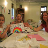 Annabel, Natalie, and Heather Saunders hold up one of the peace flags Annabel designed during Tuesday night's workshop at The Graceful Planet.    (Hicks photo)