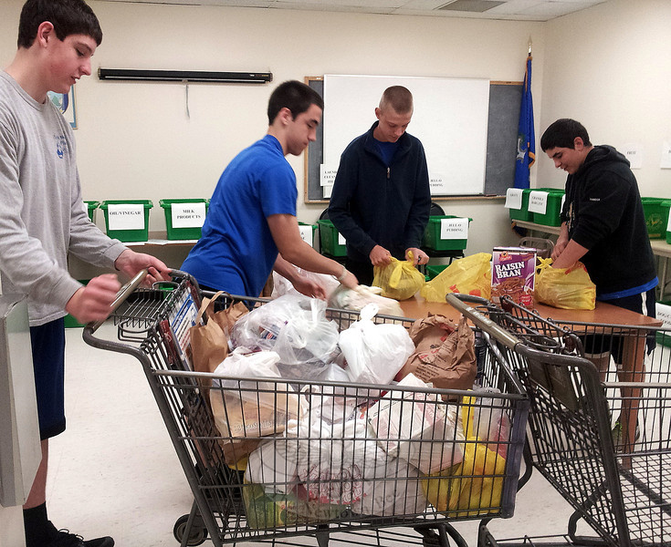 After unloading John Ogrinc's postal vehicle carrying donated food, NHS Football Team members, from left, Jake Lambert, Drew Tarantino, Jacob Burden, and Jaret Devellis got busy sorting. Case manager Ann Benore said this year's Postal Food Drive filled almost 90 recycling bins with close to a ton of food. As a result, she said, the local Salvation Army Food Pantry should be well stocked through the summer months.   (Voket photo)