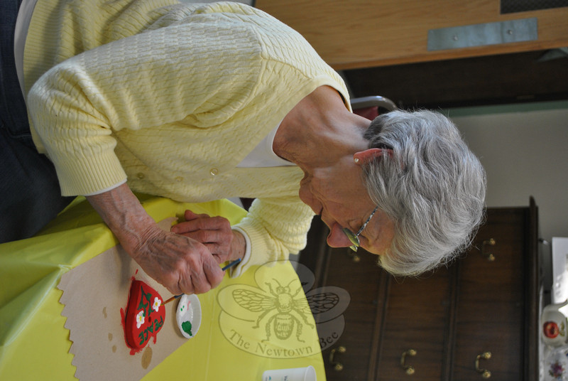 """Newtown resident Marlene Whitney painted a Hearts of Hope ceramic heart on Thursday, May 9, at a Newtown Senior Center workshop to support the project that sent Hearts of Hope to Boston, following the April 15 Boston Marathon bombings.  (Crevier photo)<br /> <br /> PLEASE NOTE: Additional photos for this story, which were presented online in a slideshow, can be viewed here: <a href=""""http://newtownbee.smugmug.com/Journalism/Special-Events/With-Painted-Ceramic-Hearts/29588277_K95HcF/#!i=2530875896&k=GZVLFV6"""">http://newtownbee.smugmug.com/Journalism/Special-Events/With-Painted-Ceramic-Hearts/29588277_K95HcF/#!i=2530875896&k=GZVLFV6</a>"""