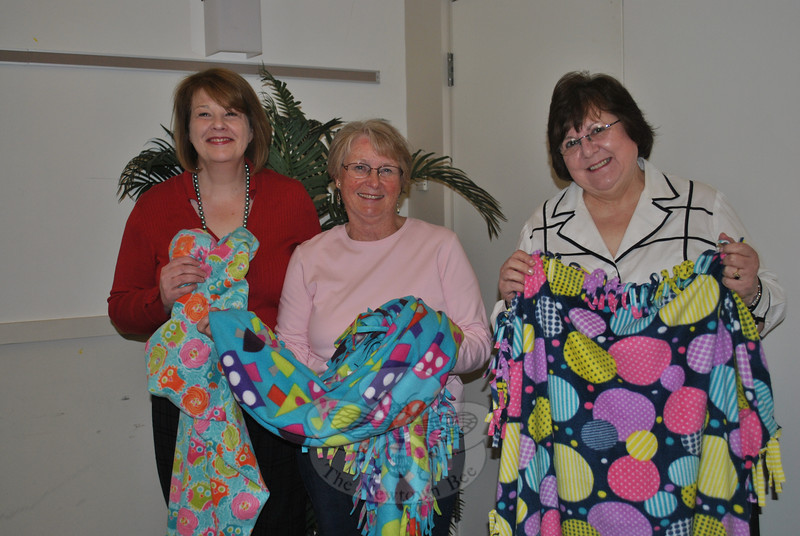 From left, Joan Duffy of the Connecticut GFWC, Inc, and Newtown Woman's Club co-presidents Shirley Ferris and Nina Morrisson display samples of the 26 colorful fleece throw received by the local organization, through a joint effort of a Minnesota GFWC and school class project.   (Crevier photo)