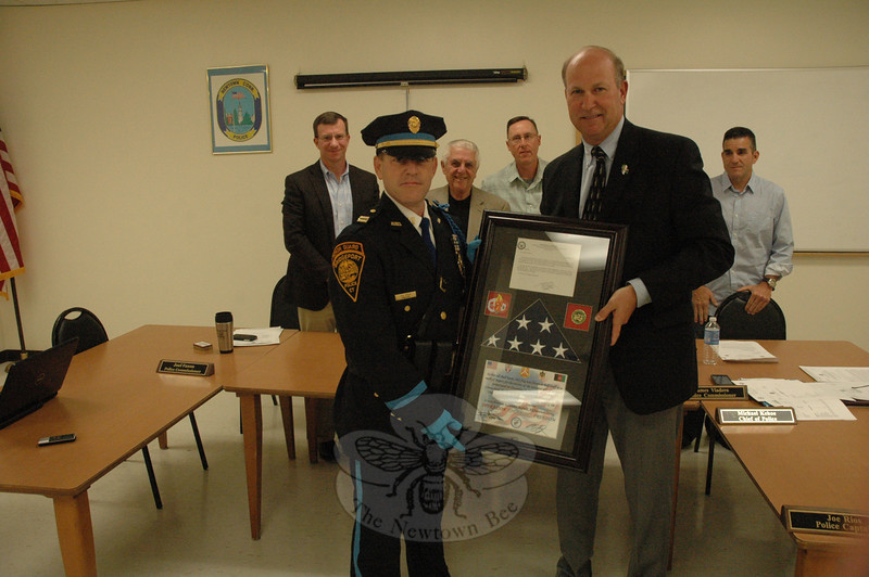 At the June 4 Police Commission meeting, Bridgeport Police Captain Douglas Stolze, left foreground, presented a commemorative plaque containing a folded US flag to Newtown Police Chief Michael Kehoe as the commission members, background, looked on. From left, are Joel Faxon, Chairman Paul Mangiafico, Brian Budd, and James Viadero. The US Army's flag was flown at half staff at Kandahar Airfield in Afghanistan in observance of those who lost their lives 12/14. A letter from the US Army's 101st Expeditionary Signal Battalion in Afghanistan offers its condolences to the town.    (Gorosko photo)