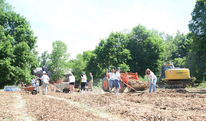 Volunteers spread mulch that will help keep the weeds down between garden rows. The group was working as part of the United Way of Western Connecticut's annual Day of Action.   (Bobowick photo)