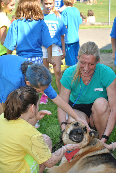 Enthusiasm was as high as the temperature, Friday, May 31, as Head O' Meadow Elementary School students gathered in the field behind the school to take part in Spirit Day. Students gather around comfort dog, Jessie, and her handler Maureen Birdins.   (Crevier photo)