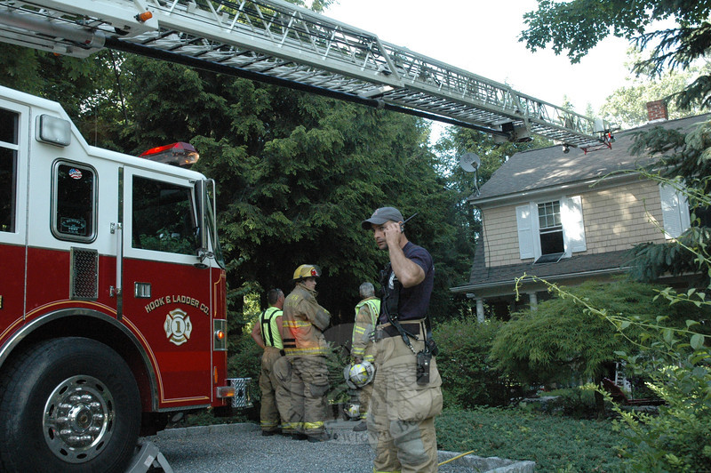 Hook & Ladder Fire Chief Ray Corbo speaks on a two-way fire radio at the scene of a house fire at 19 Borough Lane on the evening of Wednesday, June 5. An electrical problem caused a fire that extensively damaged a family room in the home's basement and caused smoke damage to the rest of the two-story house.   (Gorosko photo)
