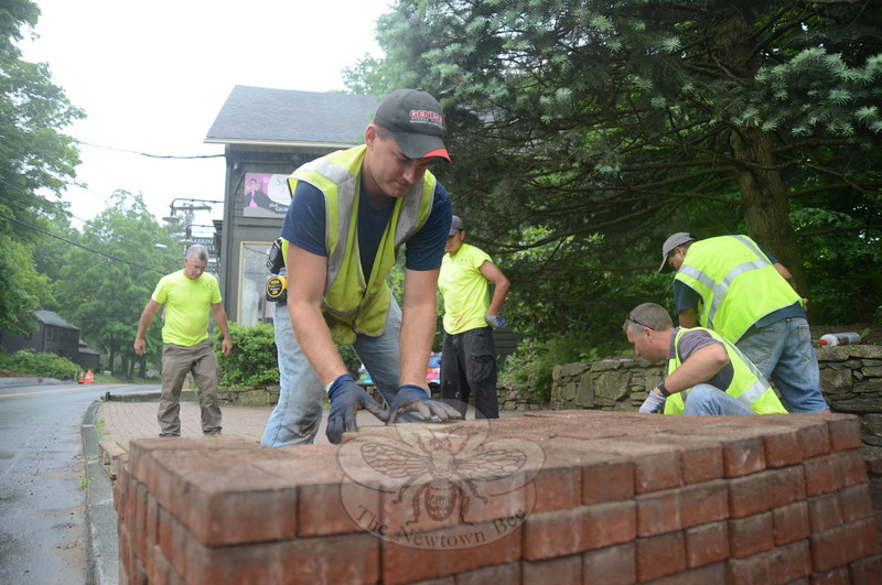 Ryan Clark stacks old bricks from a walkway in Sandy Hook Center. He and others with LRM Inc, including Mike Burton, left, and Rob Manna, right, pull up the old bricks that will be used in future Sandy Hook projects.  (Bobowick photo)